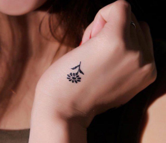ideas de tatuajes pequeños y bonitos en imágines, pequeña flor tatuada en la mano, diseños simbólicos