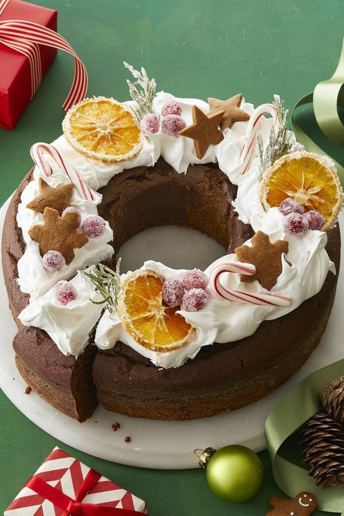 tarta de chocolate decorada con nata, galletas jengibre, rebanadas de naranja y frutas azucaradas