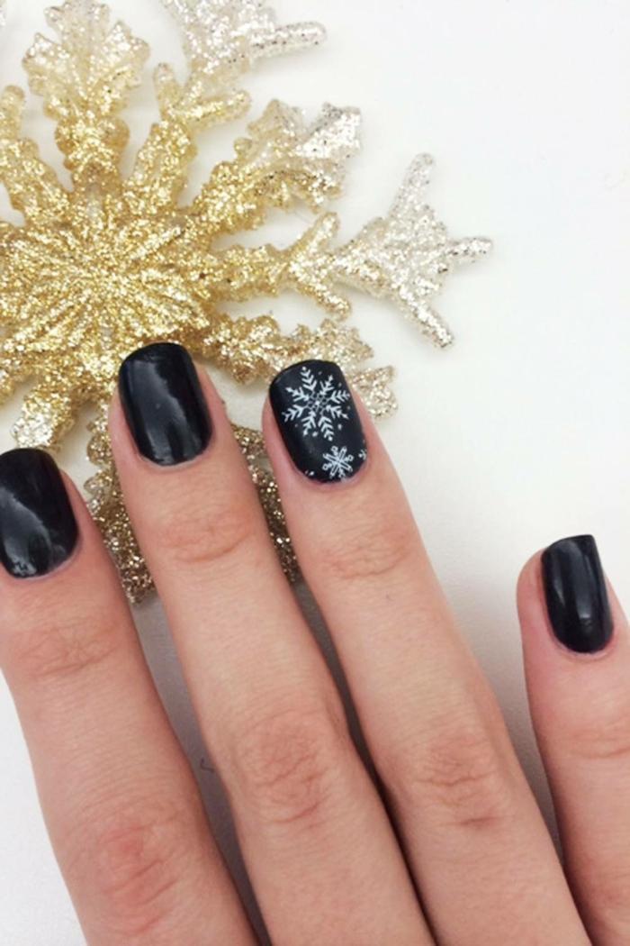 diseños de uñas en blanco y negro para navidad, uñas cortas pintadas en negro con dibujos de copos de nieve