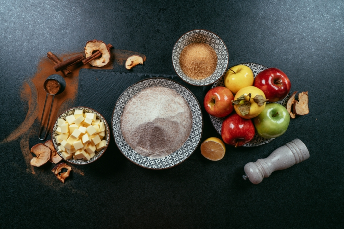 los ingredientes necesarios para hacer una tarta de manzanas casera, mantequilla ablandada, harina integral, azucar de coco