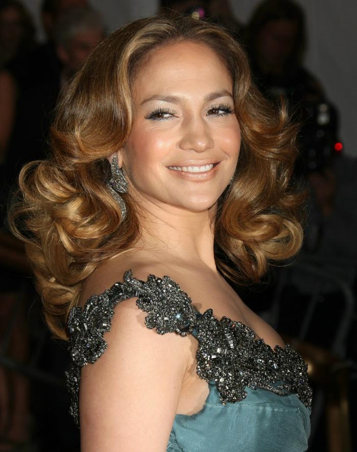 Jennifer Lopez luciendo media melena con grandes bucles bien definidos, cabello rubio oscuro con mechas mas claras