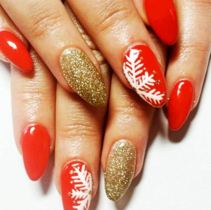 uñas largas con forma de almendra afiladas, manicura en rojo brillante y dorado, dibujos de copos de nieve en blanco