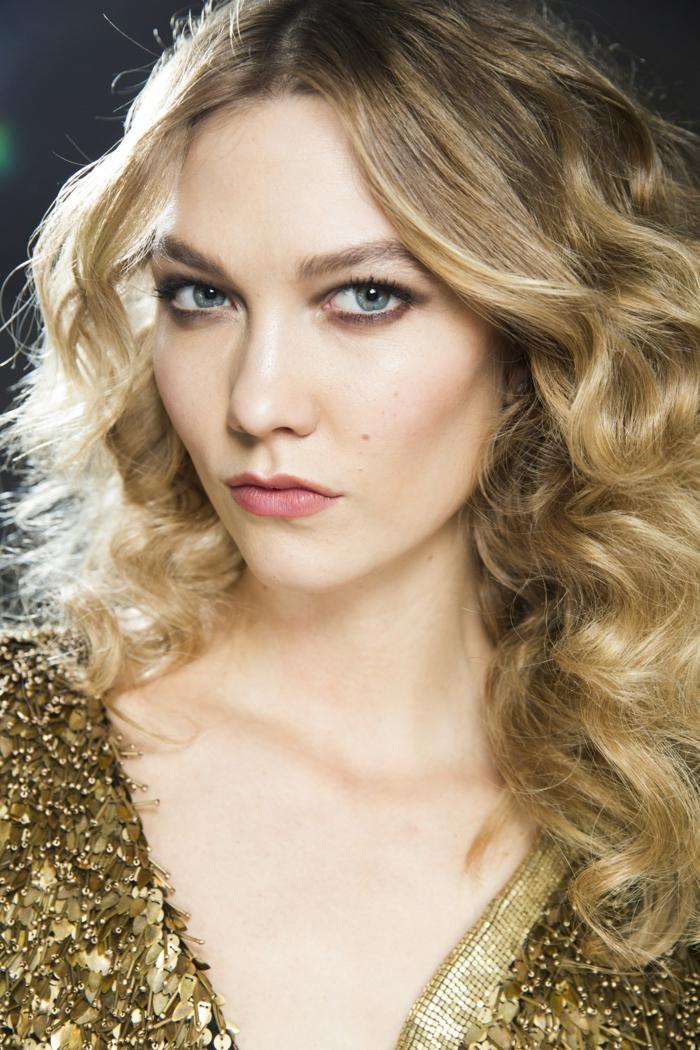 cabello rizado con mucho volumen, media melena rubia con raices oscuros, vestido con lentejuelas en dorado