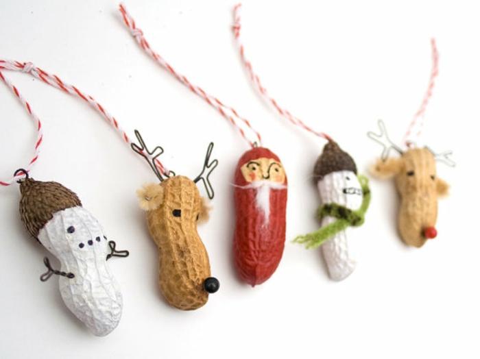 mini adornos hechos de cáscaras de cacahuetes decoradas, ideas para adornar un arbol de navidad casero