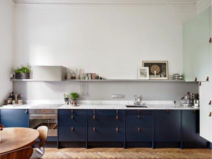 cocina decorada en estilo moderno con suelo de parquet y armarios en gris oscuro, paredes blancas