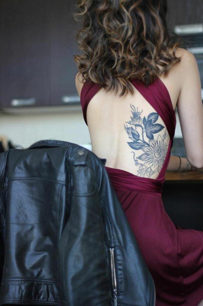 bonitos diseños de tattoos para mujeres con motivos florales, tatuaje flor en la espalda