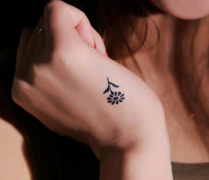adorable tatuaje flor de tamaño super pequeño en la mano, pequeña margarita en negro