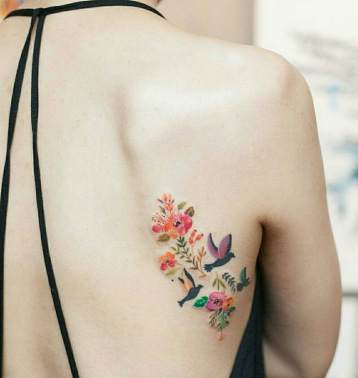 preciosos tatuajes de flores en colores, tatuaje con flores coloridas y aves en pleno vuelo