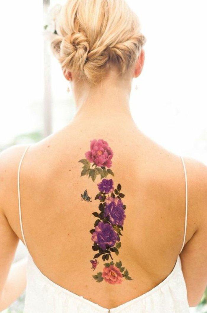 adorable diseño con flores en rosado y lila en la espalda, tatuajes de flores bonitos para mujeres