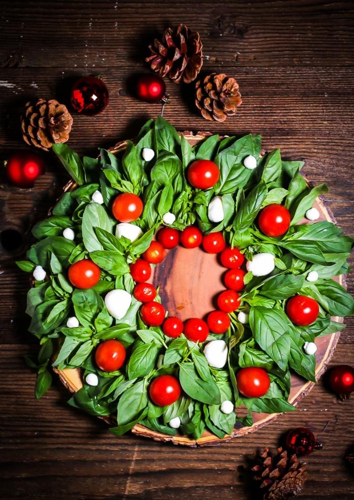 ensalada caprese en forma de corona de navidad, trozos de mozzarella, mini tomates y albahacas frescas, recetas originales con fotos