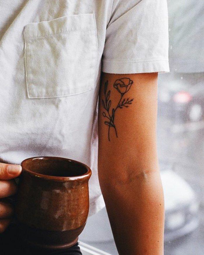 pequeño detalle con flor tatuado en el antebrazo, tatuajes de rosas bonitos en color negro