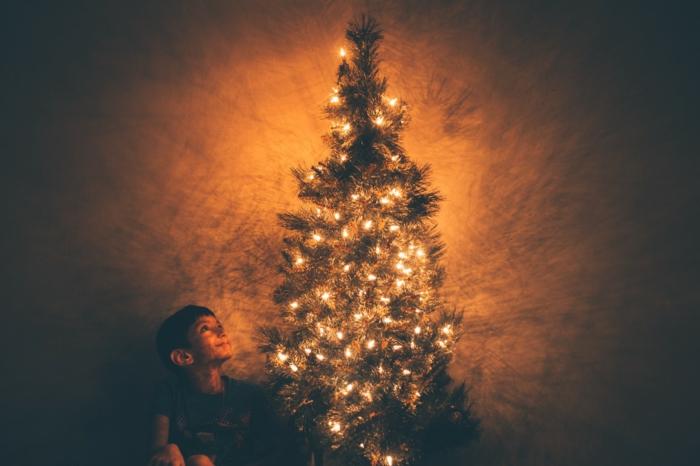 magicas fotos de Navidad, pequeño niño sentado debajo del árbol navideño, postales de navidad originales