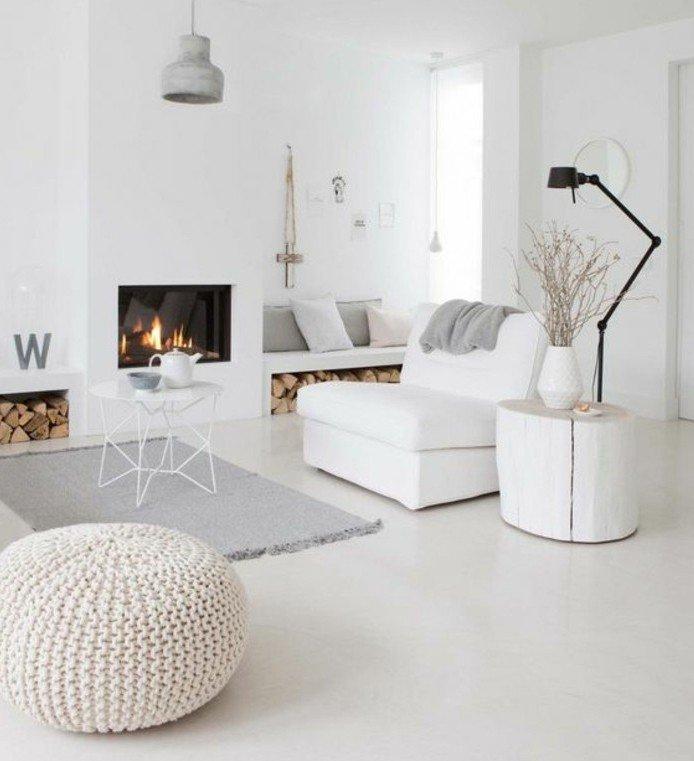 habitacion gris y blancaco con chimenea de leña decorada según la últimas tendencias