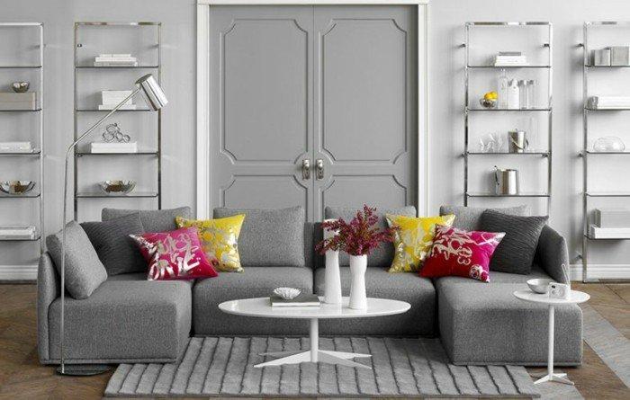 habitacion gris y blanca con cojines decorativos en amarillo y rojo, estanterías modernas