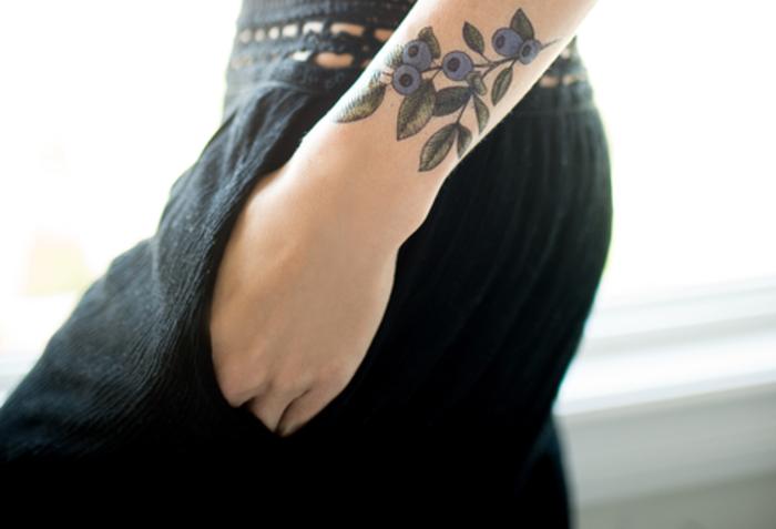 adorable tatuaje en el antebrazo, diseños de tatuajes con motivos florales, significado de las flores