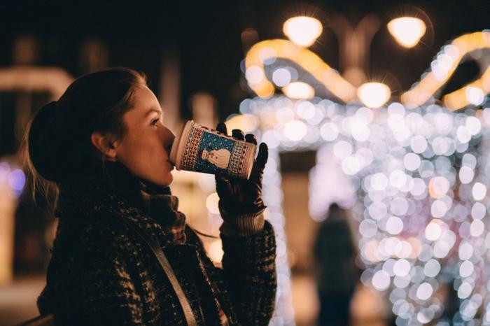paisajes de navidad inspiradores, chica bebiendo chocolate caliente, bonitas luces navideñas