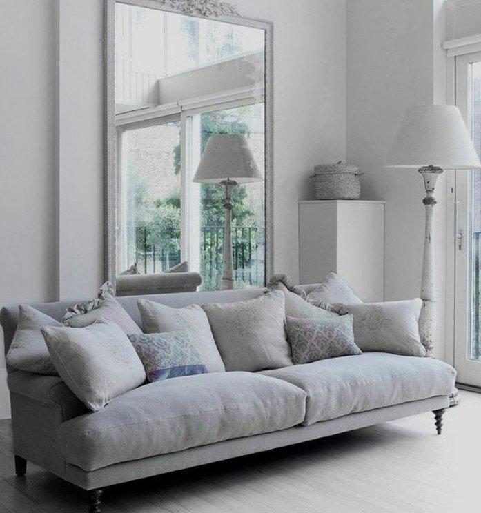 habitación gris y blanca decoraca según las últimas tendencias, grande sofá y espejo vintage