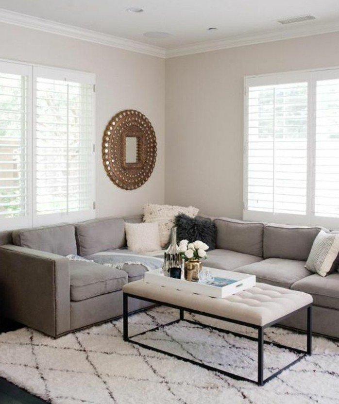 ambiente decorado en blanco y gris con espejo vintage en la pared, mesa con capitoné