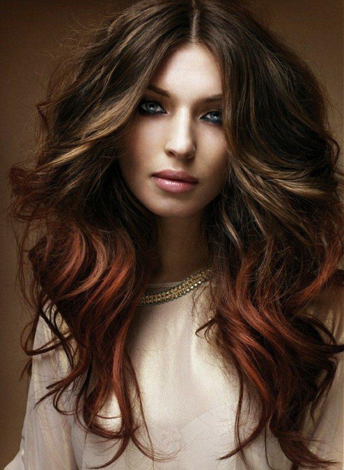 castaño oscuro con mechas rubias y rojas, pelo largo con mucho volumen y rizos