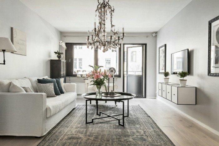 habitación gris y blanca decorada e nestilo vintage, mesa de metal y jarrón con flores, espacio moderno en gris