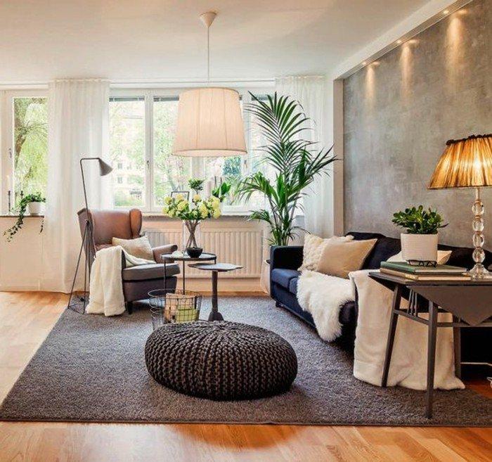espacio decorado en tonos terrosos, luces empotradas, paredes de hormigón y alfombra gris, decoracion de salones pequeños