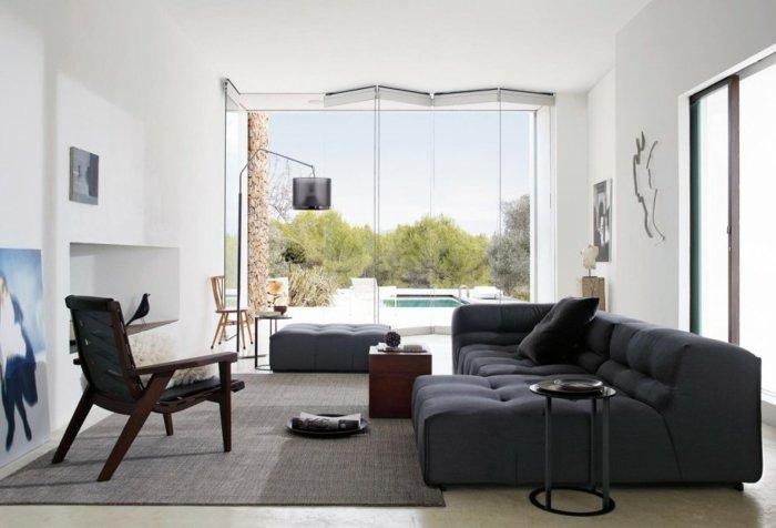 preciosa habitación gris y blanca con mucha luz, muebles en gris oscuro y paredes blancas