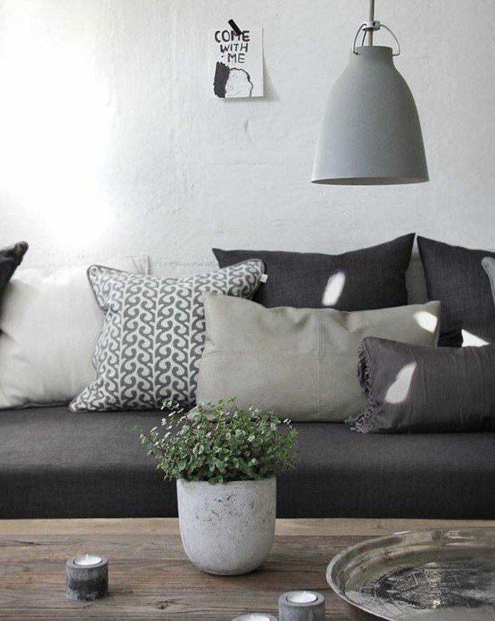 salon gris y blanco decorado en estilo escandinavo y decoración minimalista, sofá en gris oscuro, cojines decorativos