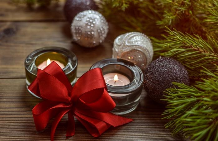 detalles navideños bonitos en fotos de Navidad, velas con adornos de navidad y moño rojo