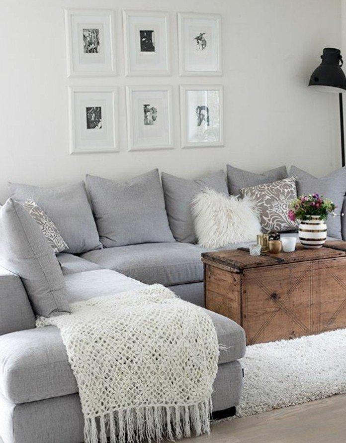 salon gris y blanco con muchos cuadros en la pared, sofá en gris claro y almohadas decorativas