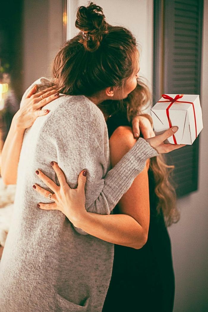 dos amigas en abrazo regalando regalos una a otra, tarjetas de navidad originales descargables