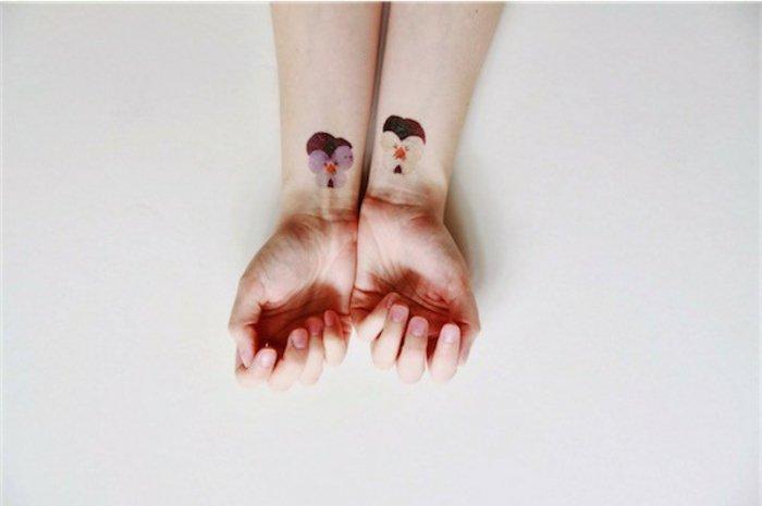 ideas de diseños de tatuajes para hermanas y significado de las flores, tatuajes con violetas en las muñecas