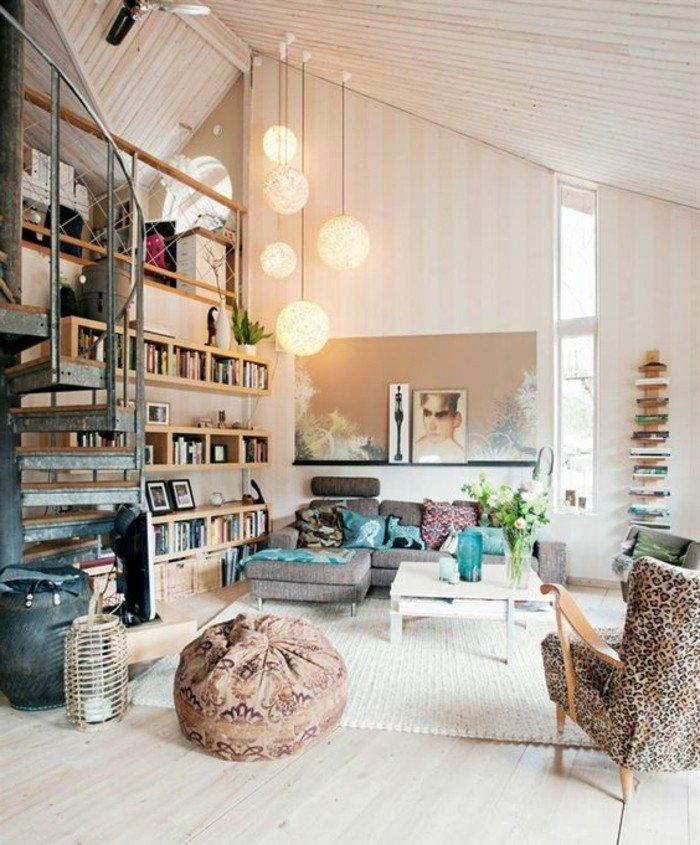 precioso salón con techo inclinado decorado en estilo bohemio, estanterías con libros, sillones