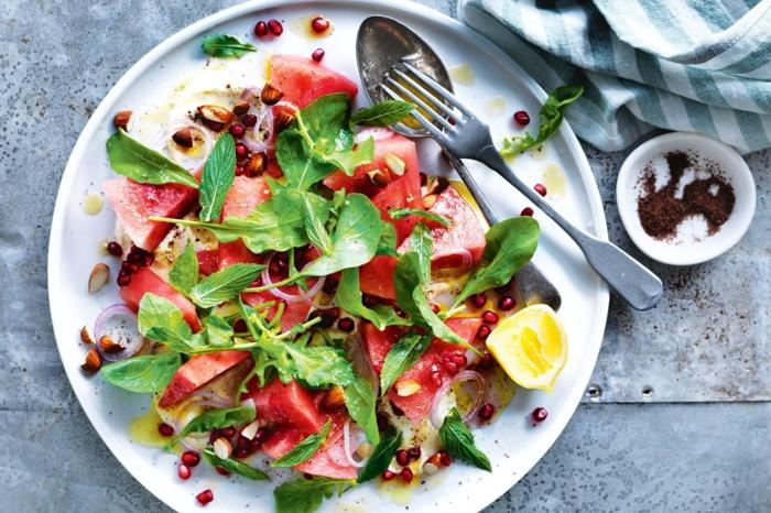 ensaladas ligeras y saludables con frutas y verduras, rucola, trozos de sandia, limon y granada