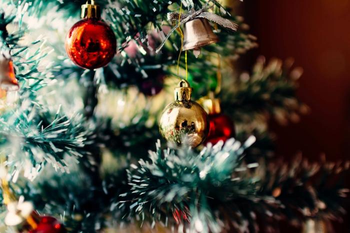 árbol navideño artificial con efecto de nevado adornado de preciosas bolas de navidad en rojo y dorado