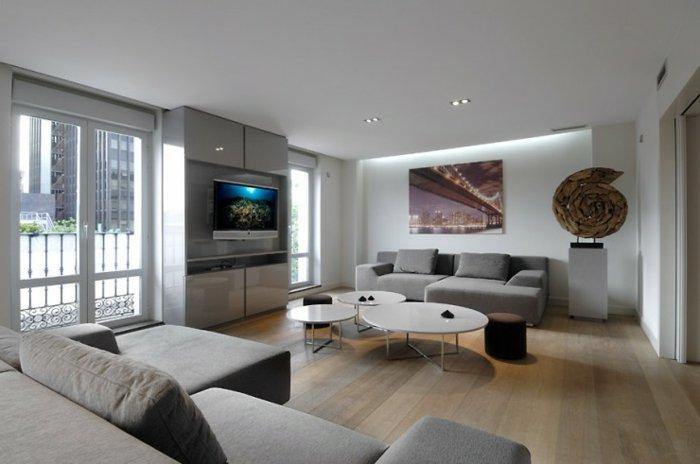 grande salón moderno con sofá en color gris perla, suelo de parquet y paredes blancas
