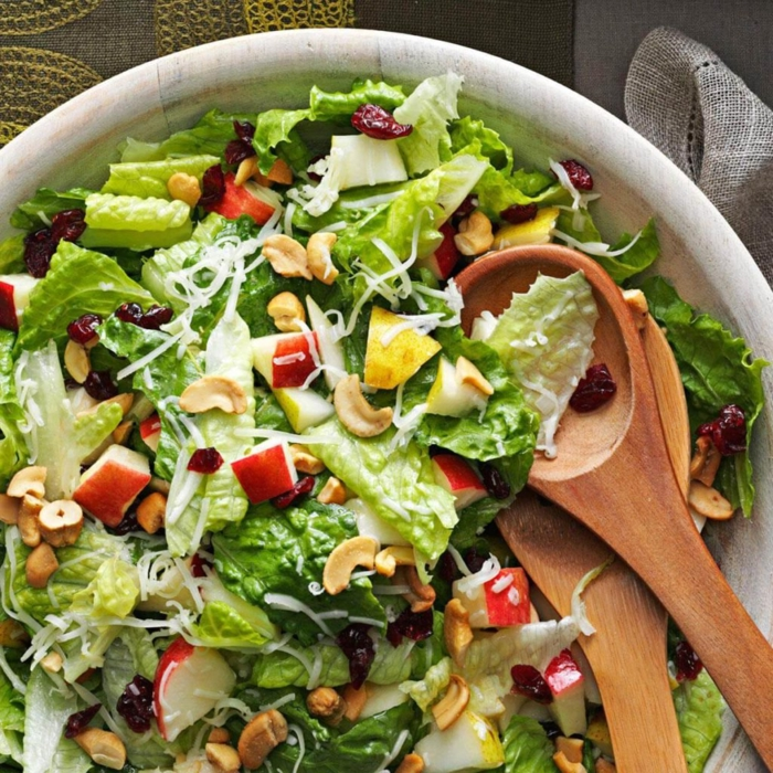 rica ensalada con lechugas verdes, trozos de manzana, anacardos, peras y queso rallado