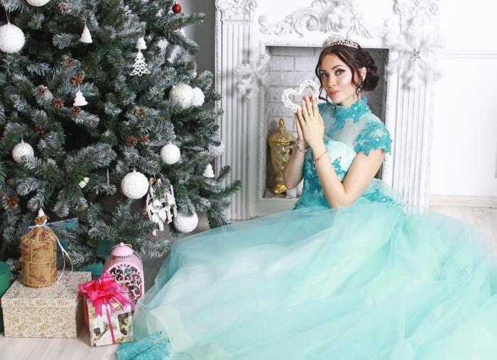 mujer con precioso vestido de tul azul, árbol navideño grande decorado de bolas en blanco