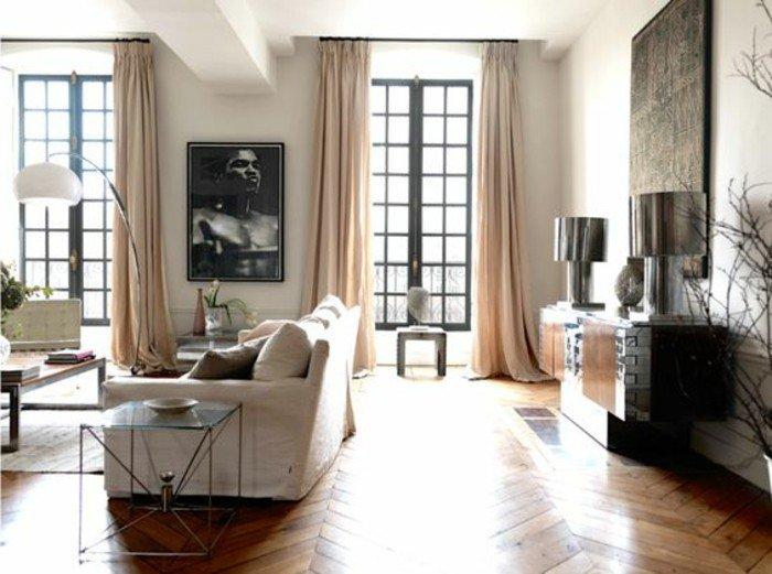 grande salón decorado en colores claros, cortinas largas en beige, suelo de parquet, sofá blanca