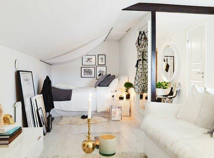 salon comedor pequeño con techo inclinado decorado en blanco, muchos objetos decorativos