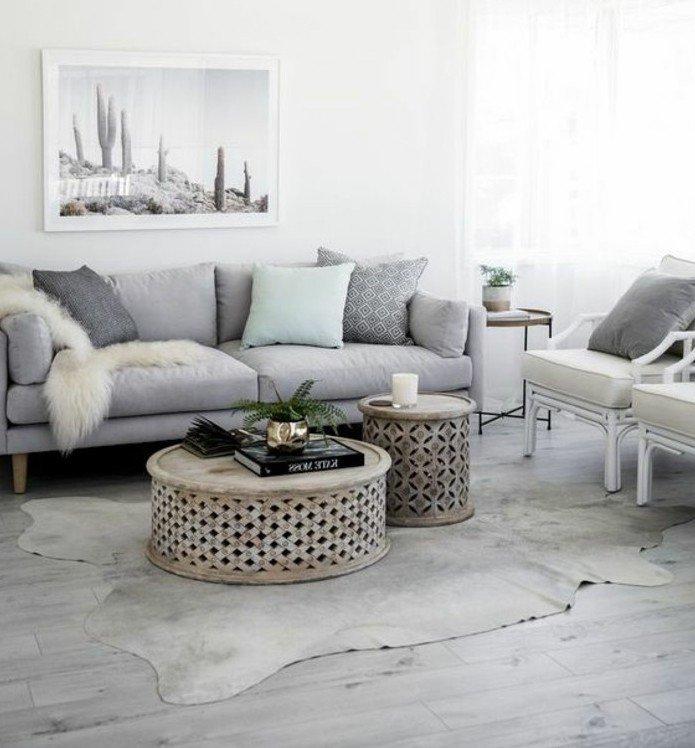 habitacion gris con paredes blancas, grande pintura en la pared y sofá gris, almohadas y cojines decorativos