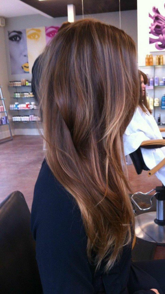 larga cabellera en color castaño oscuro con mechas mas claras, pelo castaño oscuro
