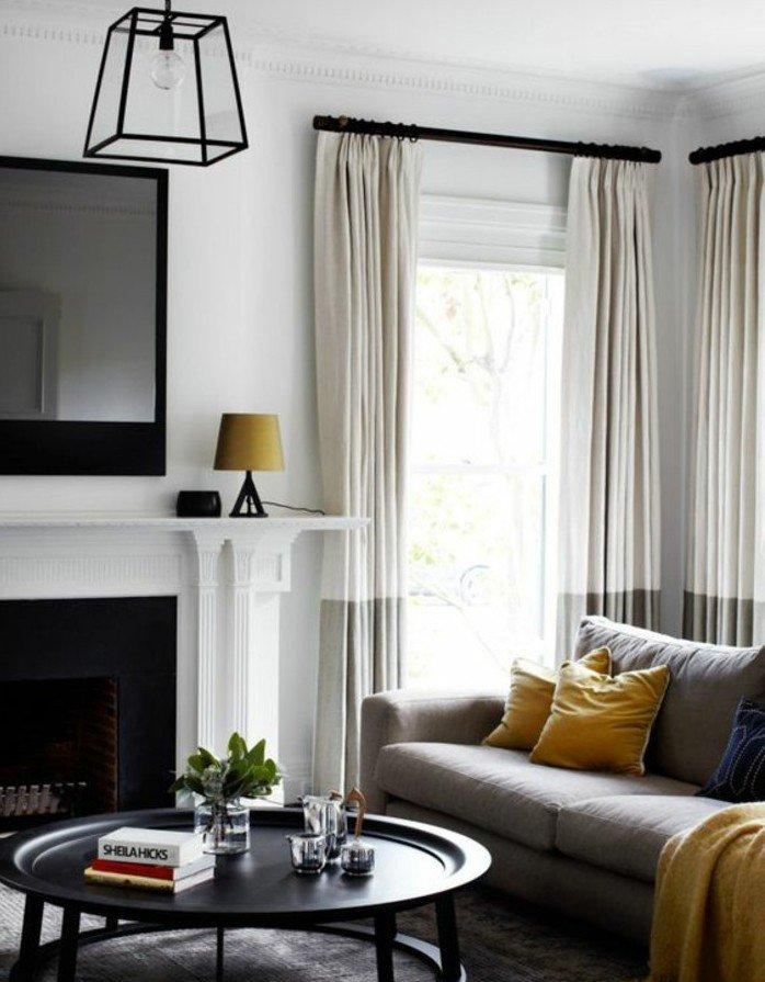 salones grises de diseño con detalles en blanco beige, lámpara moderna en negro y detalles en color mostaza