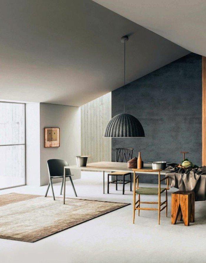 salón en estilo industrial con pared de hormigón y techo inclinado, alfombra en beige
