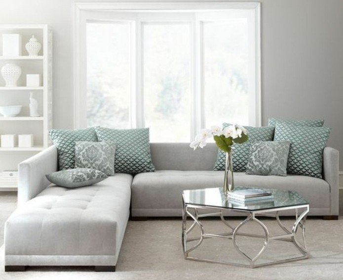 salón con paredes grises y sofá de diseño, cojines y almohadas decorativos en color verde menta