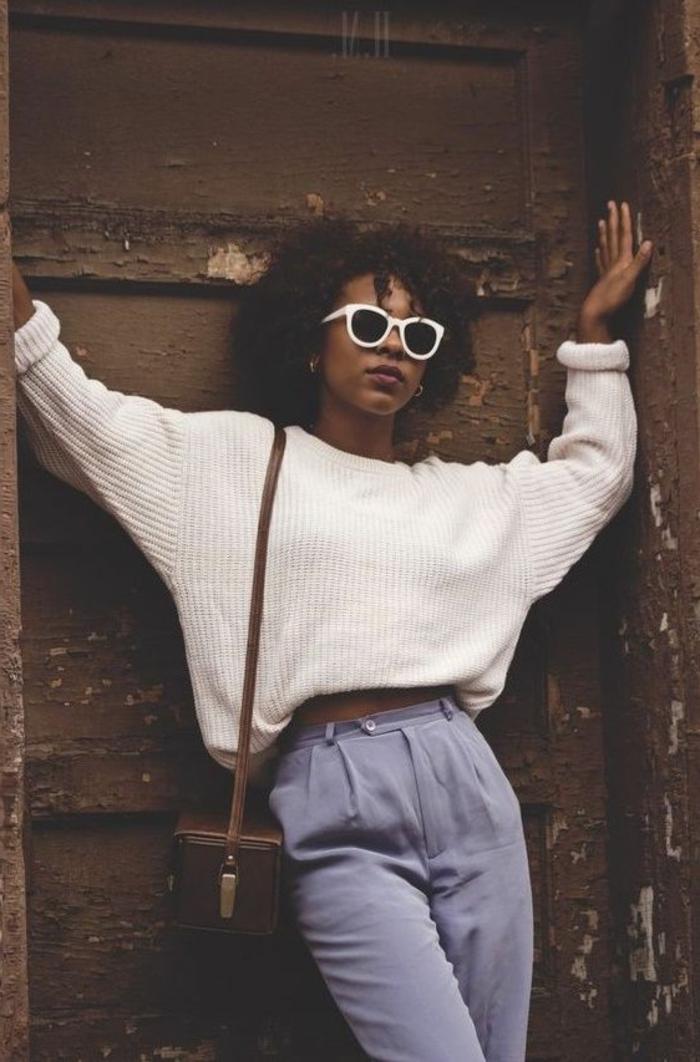 outfit vintage moda de los 80, pantalon azul y jersey en color blanco, pequeño bolso de cuero color marrón