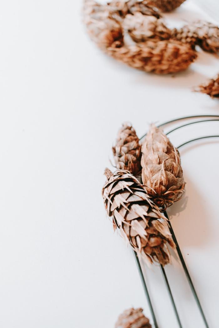 cómo hacer regalos originales para novios caseros paso a paso, corona decorativa hecha de corazon de alambre y piñas