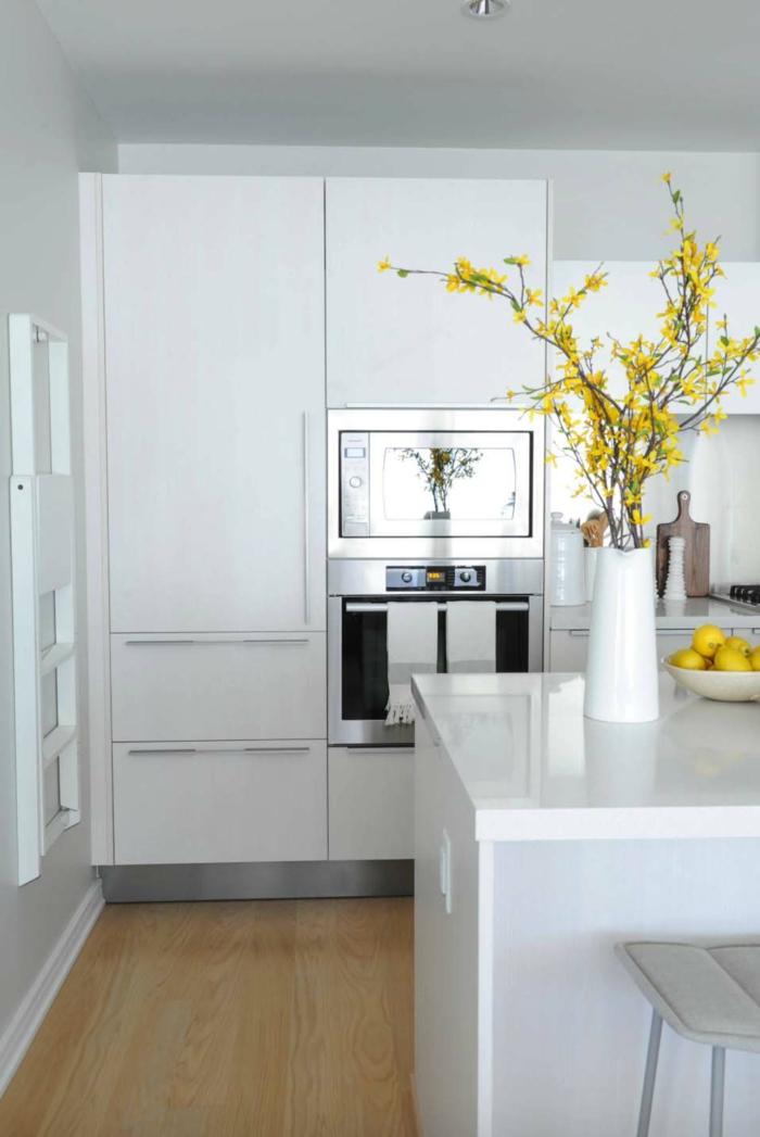 fotos de cocinas blancas pequeñas de diseño, larga isla en color blanco, suelo de parquet y muebles blancos