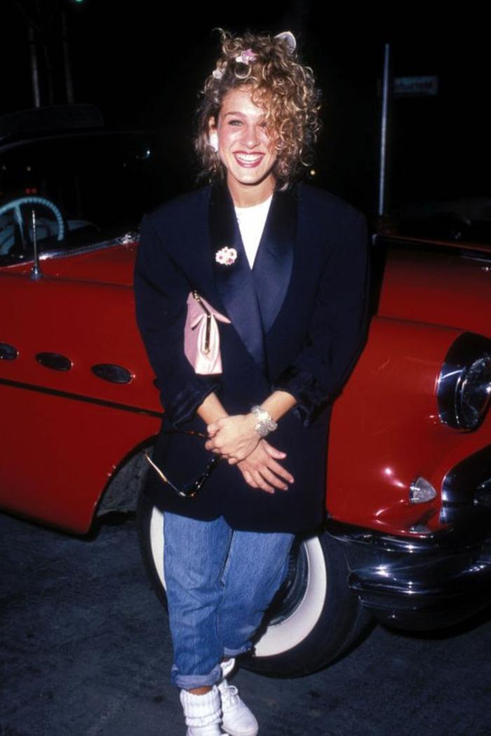 Sarah Jessica Parker con outfit del vestuario de los 80, chaqueta larga y ancha en color azul oscuro y vaqueros