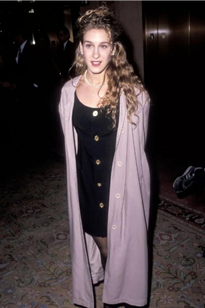 Sarrah Jessica Parker con un vestido negro corto con botones en dorado, larga chaqueta en rosado