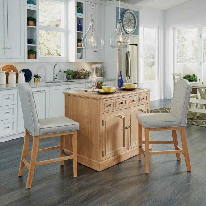 cocina decorada en blanco con muebles de madera, suelo de parquet y lámparas de diseño moderno